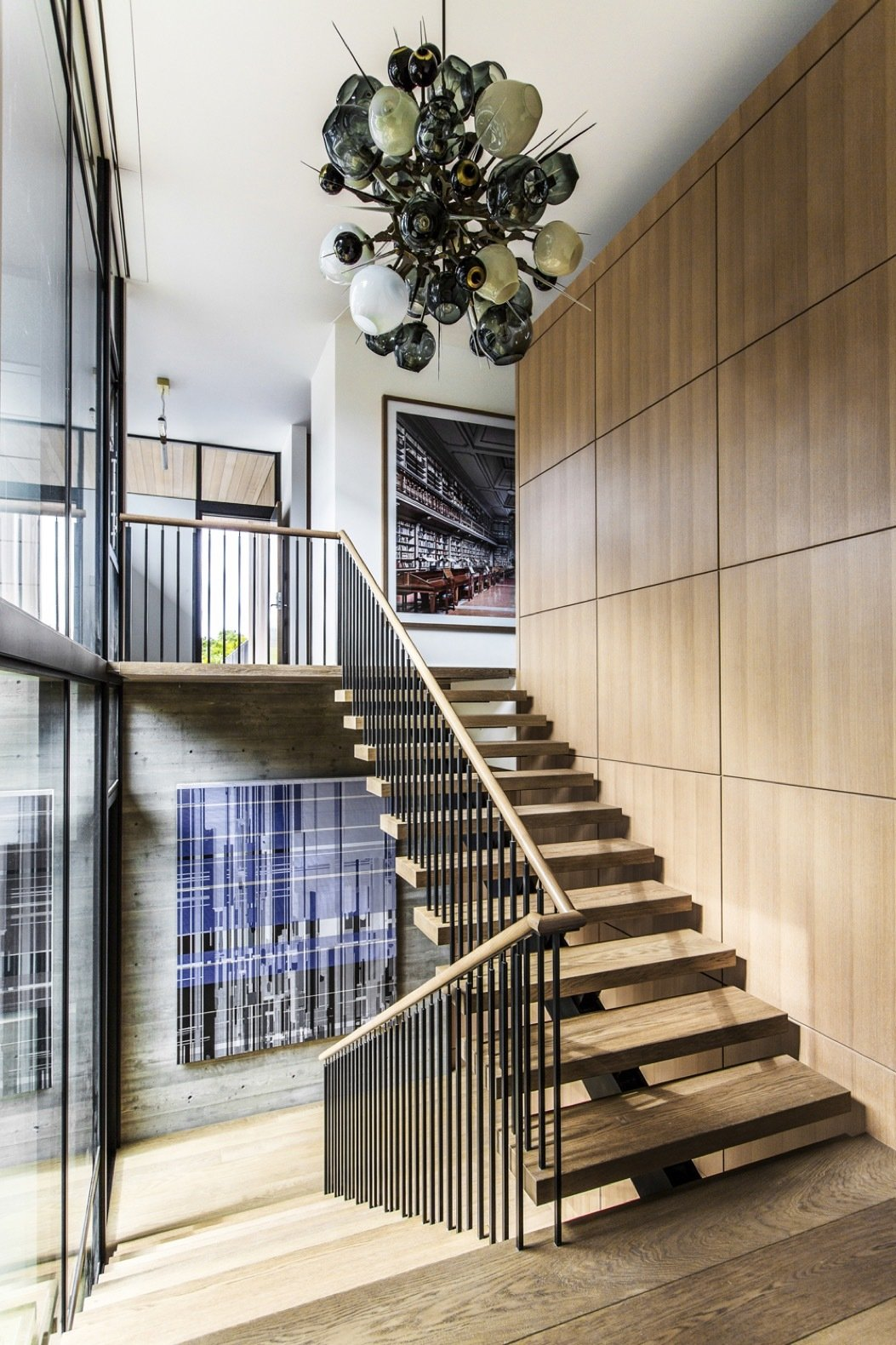Staircase, Wood Tread, and Wood Railing The home was designed to complement the clients' extensive contemporary art collection. The pendant lighting fixture is by Lindsey Adelman Studio.  Photo 5 of 14 in An Energy-Conscious Home Gets Woven Into a Waterfront Landscape