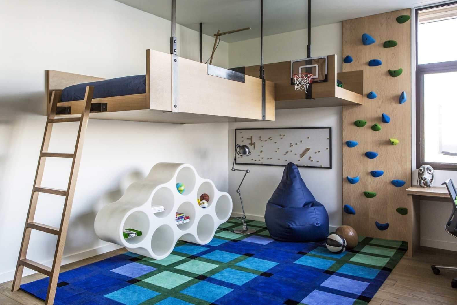 Bedroom, Medium Hardwood Floor, Bed, and Chair The clients' teenage son was given a more colorful bedroom with an elevated bed and a small climbing wall.   Photo 11 of 14 in An Energy-Conscious Home Gets Woven Into a Waterfront Landscape