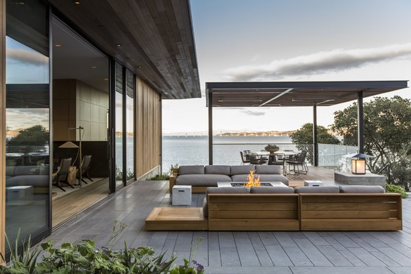 The outdoor terrace is paved with honed basaltina. The teak outdoor sofas arranged around the fire pit are by James Perse.
