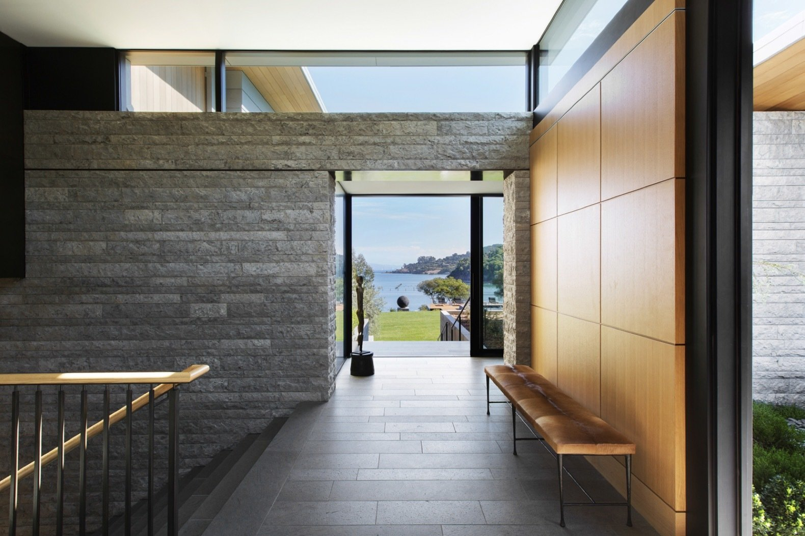 Hallway Aegean limestone continues from the exterior to the interior to create an indoor/outdoor connection.   Photo 4 of 14 in An Energy-Conscious Home Gets Woven Into a Waterfront Landscape