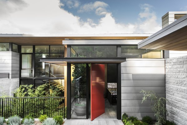 A bright red pivot door marks the main entrance, located a half-level below the upper floor.