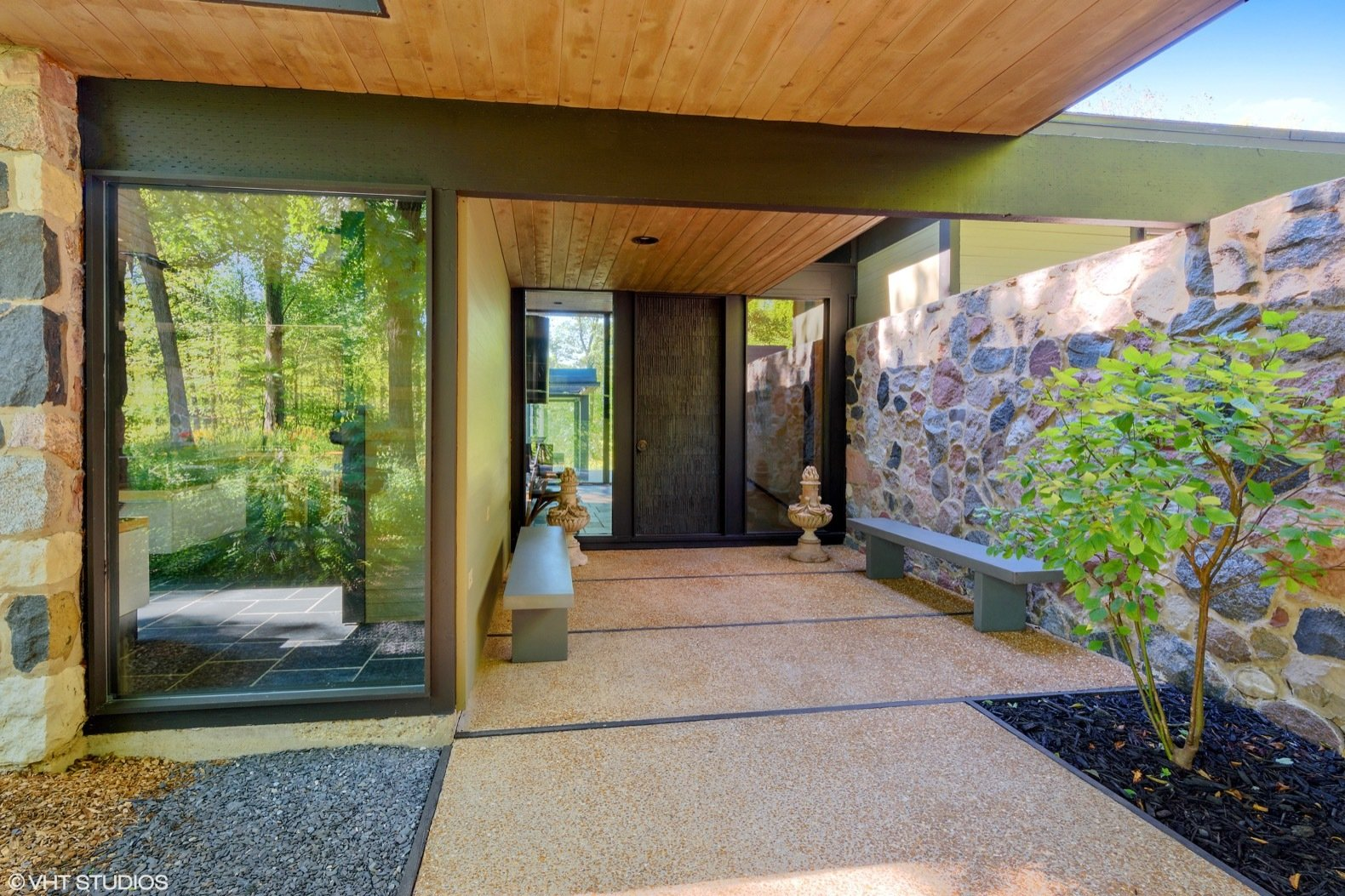 Doors, Metal, Exterior, and Swing Door Type The covered entrance walkway that leads to a oversized bronze door is bordered by a long granite wall on one side and open woodland on the other.  Photos from Own a Midcentury Gem by a Frank Lloyd Wright Disciple For $1.2M