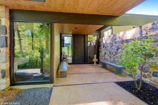 The covered entrance walkway that leads to a oversized bronze door is bordered by a long granite wall on one side and open woodland on the other.