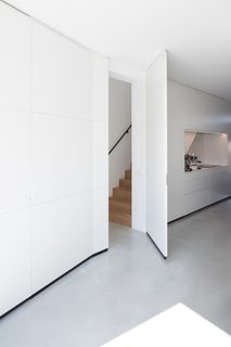 """Integrated solutions are designed for maximum openness in the house: The entrance hall, toilet, staircase, doors and kitchen are combined in a long wall cabinet that runs from the front to the rear,"" note the architects. ""It narrows and widens, creating places with a variation in atmosphere and perspective."""