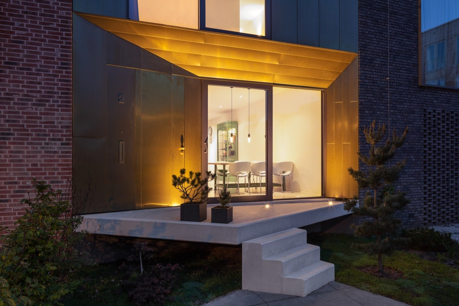Doors, Metal, Exterior, and Sliding Uplighting makes the brass facade glow gold at night.  Best Doors Metal Exterior Photos from A Sculptural Brass House Glows Like a Jewel in Amsterdam