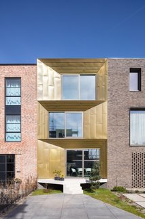 Sandwiched between two brick-clad homes, the Brass House on Haveneiland-Oost catches the eye with its angled brass facade that changes color from gold to brown in the light.
