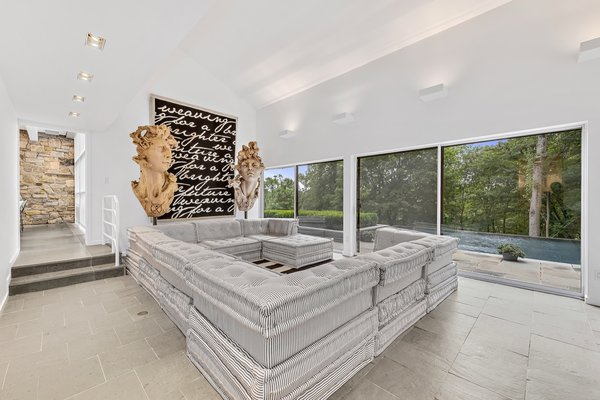 The family room in the cottage connects to the terrace and pool through massive sliding doors.