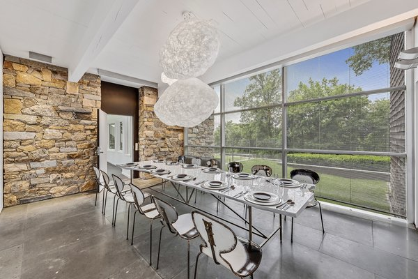 A look at the dining room in the cottage. The 30-foot-tall stone wall, which extends across multiple rooms and the outdoors, was added by the Whartons who wanted to obscure views of the cottage when inside the Shamberg House.