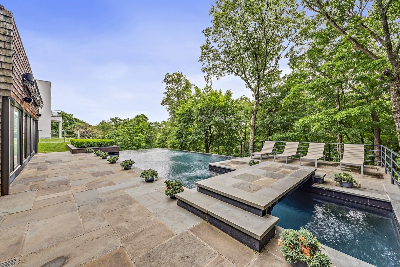 Outdoor, Stone, Back Yard, Trees, Infinity, Grass, Large, Large, Raised Planters, Swimming, Hanging, Horizontal, Shrubs, Metal, and Woodland The rear terrace boasts a recently built heated swimming pool with an infinity edge.  Outdoor Metal Stone Back Yard Hanging Photos