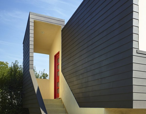 A timber door painted a vibrant red marks the sheltered entrance.