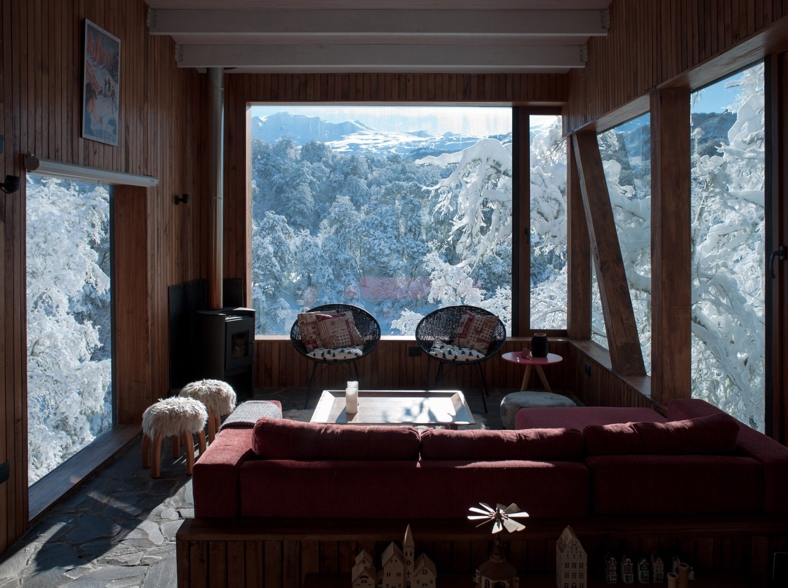 Living, Coffee Tables, Wood Burning, Chair, End Tables, Cement Tile, Stools, Sectional, Ottomans, and Wall A small wood-burning stove anchors a corner of the living room that offers straight-on views of the snow-capped volcanoes.  Best Living Ottomans Wall Photos from Wake Up to Mountain Vistas in This Chic Chalet in Chile