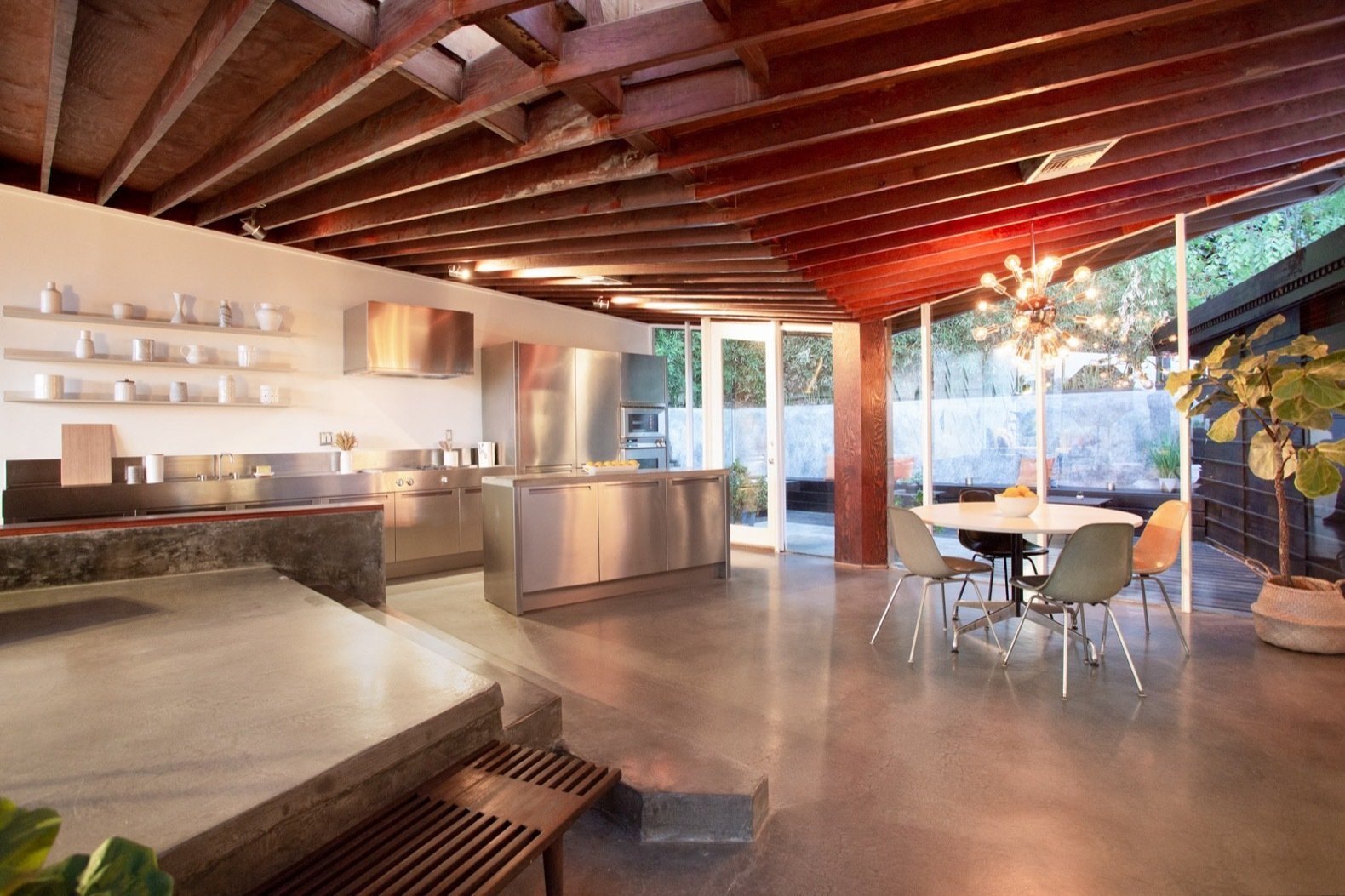 Kitchen, Accent, Wall Oven, Cooktops, Concrete, Refrigerator, Metal, Drop In, Range Hood, Concrete, Ceiling, and Pendant The kitchen features updated appliances, stainless steel countertops and a poured concrete island.   Best Kitchen Cooktops Wall Oven Range Hood Metal Photos from Grab This Sleek L.A. Midcentury by John Lautner For Under $2M
