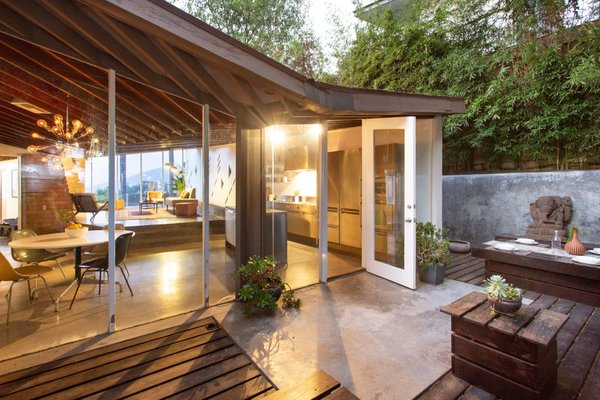 The kitchen opens up to a rear timber patio that's enclosed with bamboo and concrete walls.