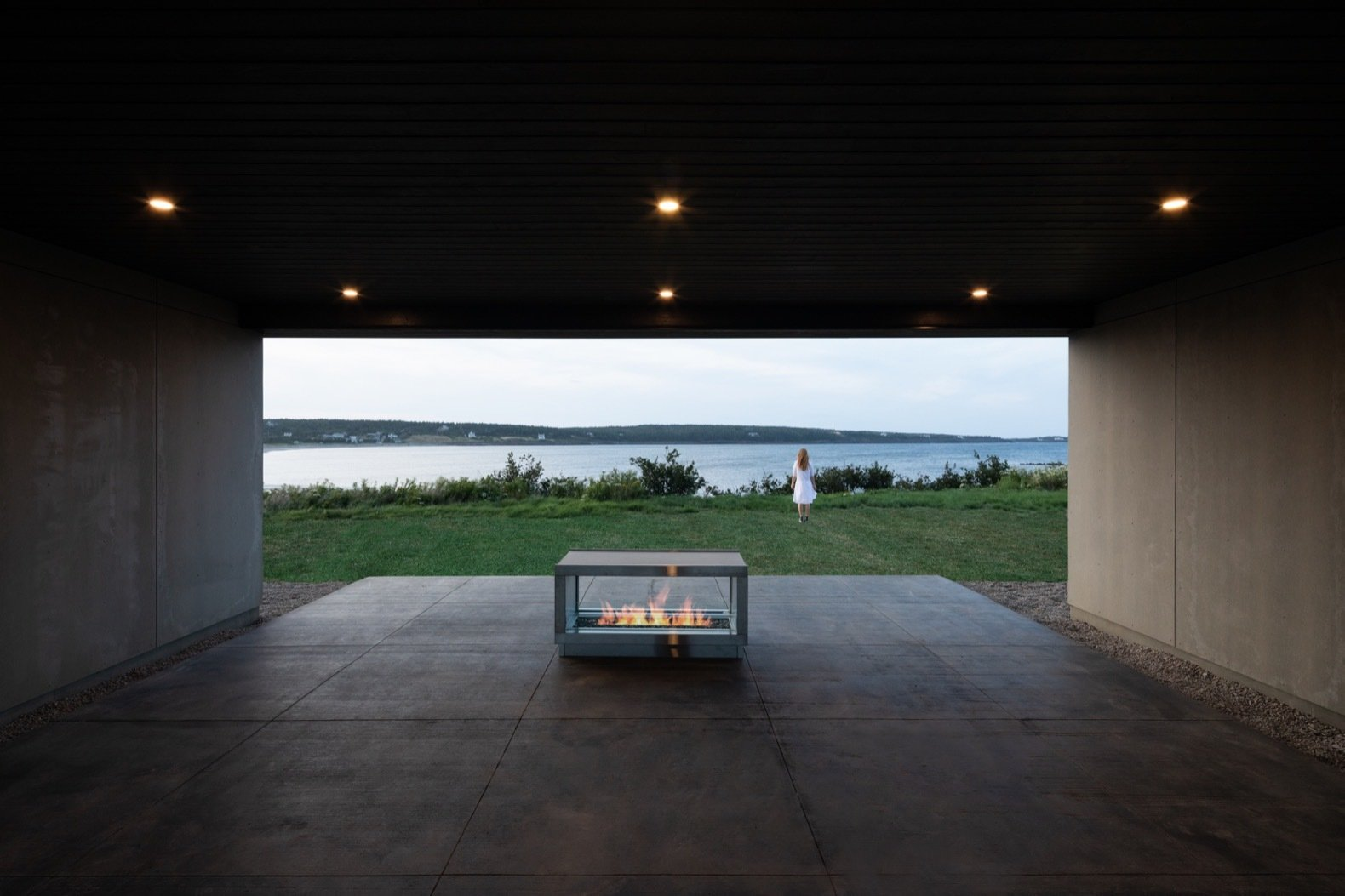 Outdoor, Grass, Large, Concrete, Walkways, Back Yard, Hanging, Concrete, and Hardscapes Connected to the plunge pool, this ground-level terrace with a fireplace is perfectly positioned for beach views.  Best Outdoor Concrete Grass Photos from A Folded Steel Roof Shields a Fortress-Like Abode in Nova Scotia