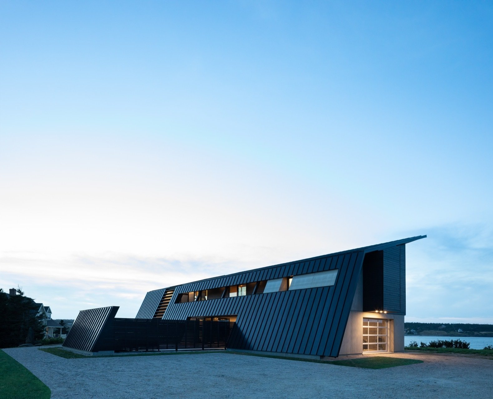 Exterior, Wood, House, Metal, Metal, Concrete, and Saltbox Extra-dark bronze standing-seam metal partly clads the home and creates an armored appearance.  Exterior Metal Saltbox Concrete Photos from A Folded Steel Roof Shields a Fortress-Like Abode in Nova Scotia
