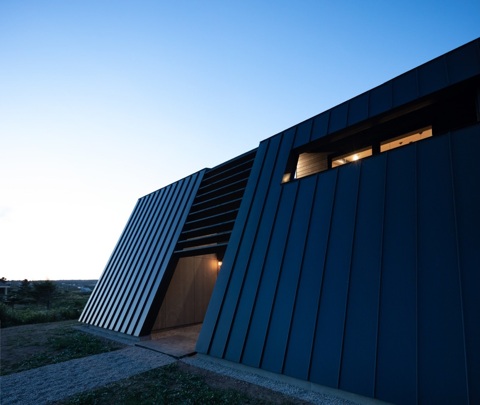 "Exterior, Metal Roof Material, House Building Type, Metal Siding Material, Concrete Siding Material, Wood Siding Material, and Saltbox RoofLine ""Both the deep-set windows and the brise soleil, in addition to the back canted wall, help to control solar gain.""  Photos from A Folded Steel Roof Shields a Fortress-Like Abode in Nova Scotia"