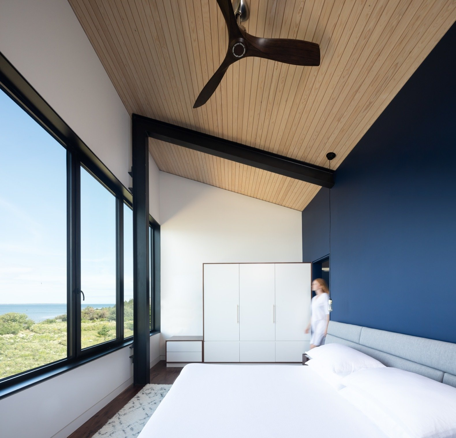 Bedroom, Dark Hardwood, Bed, Night Stands, Wardrobe, Storage, Ceiling, and Rug The master bedroom overlooks views of the water and beach through continuous glazing.  Best Bedroom Ceiling Wardrobe Bed Photos from A Folded Steel Roof Shields a Fortress-Like Abode in Nova Scotia
