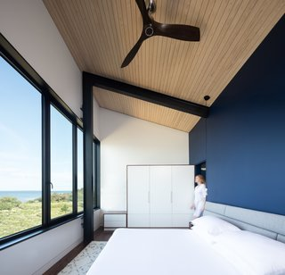 The master bedroom overlooks views of the water and beach through continuous glazing.