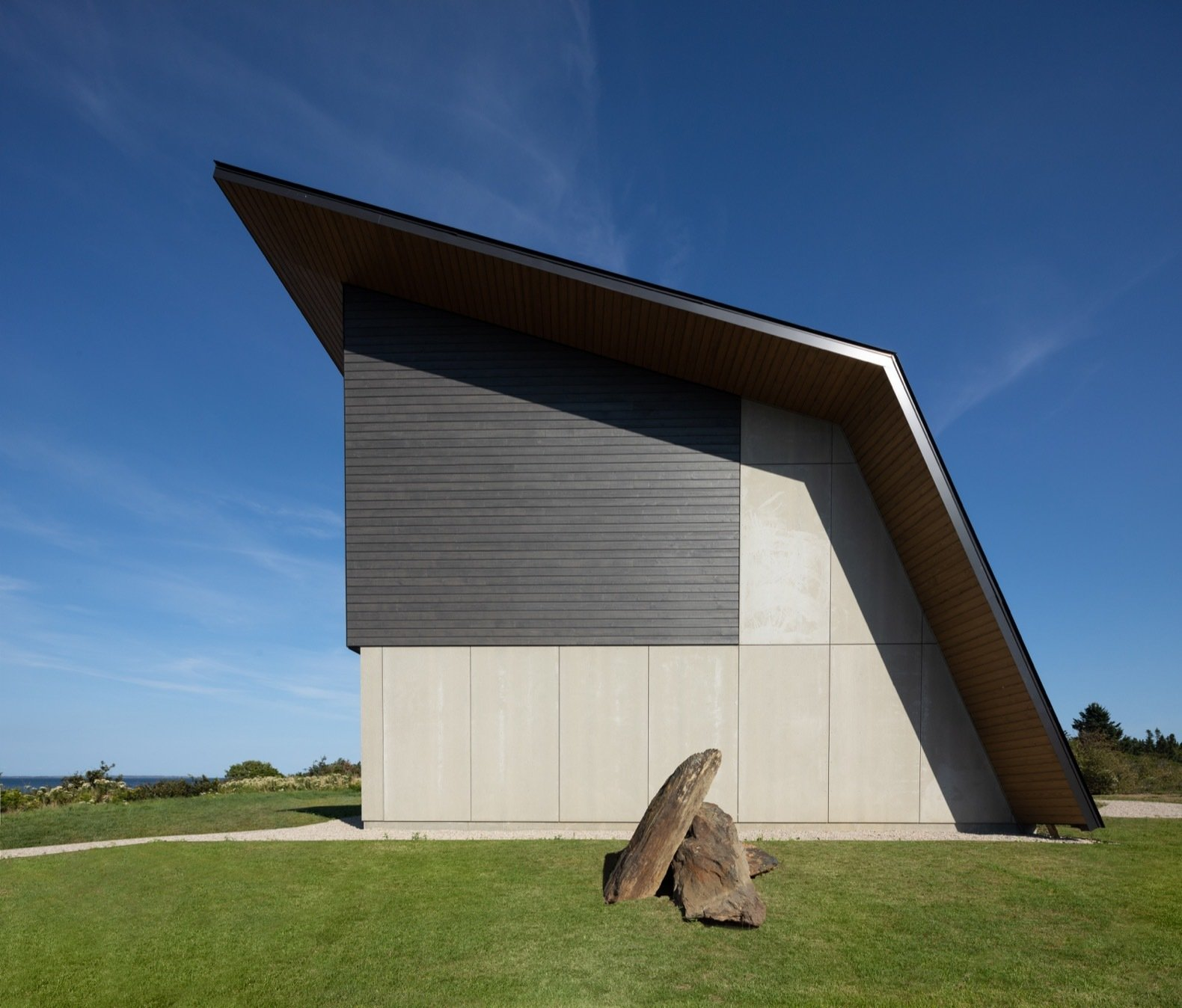 Exterior, Metal Siding Material, Wood Siding Material, House Building Type, Metal Roof Material, Concrete Siding Material, and Saltbox RoofLine In contrast to its heavily glazed north facade, the home's other three sides are closed off from view for privacy.  Photos from A Folded Steel Roof Shields a Fortress-Like Abode in Nova Scotia