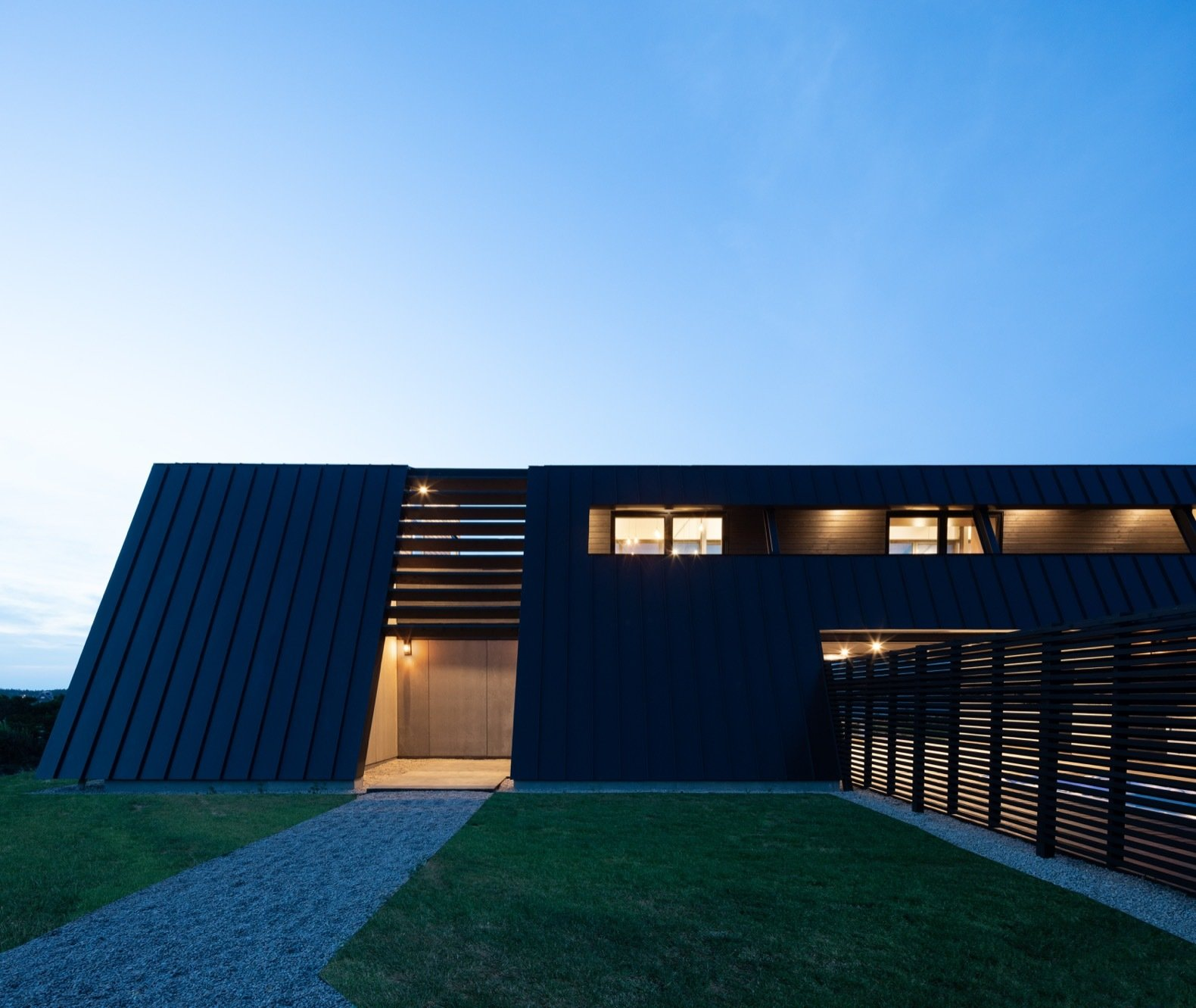 Exterior, Metal Roof Material, Wood Siding Material, House Building Type, Concrete Siding Material, Metal Siding Material, and Saltbox RoofLine A glimpse of the entrance at dusk from the south elevation. To the right is a swimming pool shielded behind wooden fencing.  Photo 9 of 19 in A Folded Steel Roof Shields a Fortress-Like Abode in Nova Scotia