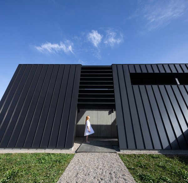 """A view of a gravel walkway and the entrance that leads to a covered pathway. """"The entry side is hyper minimal and mysterious with slight glimpses out from within, providing only a tease on approach from the road,"""" says the firm."""