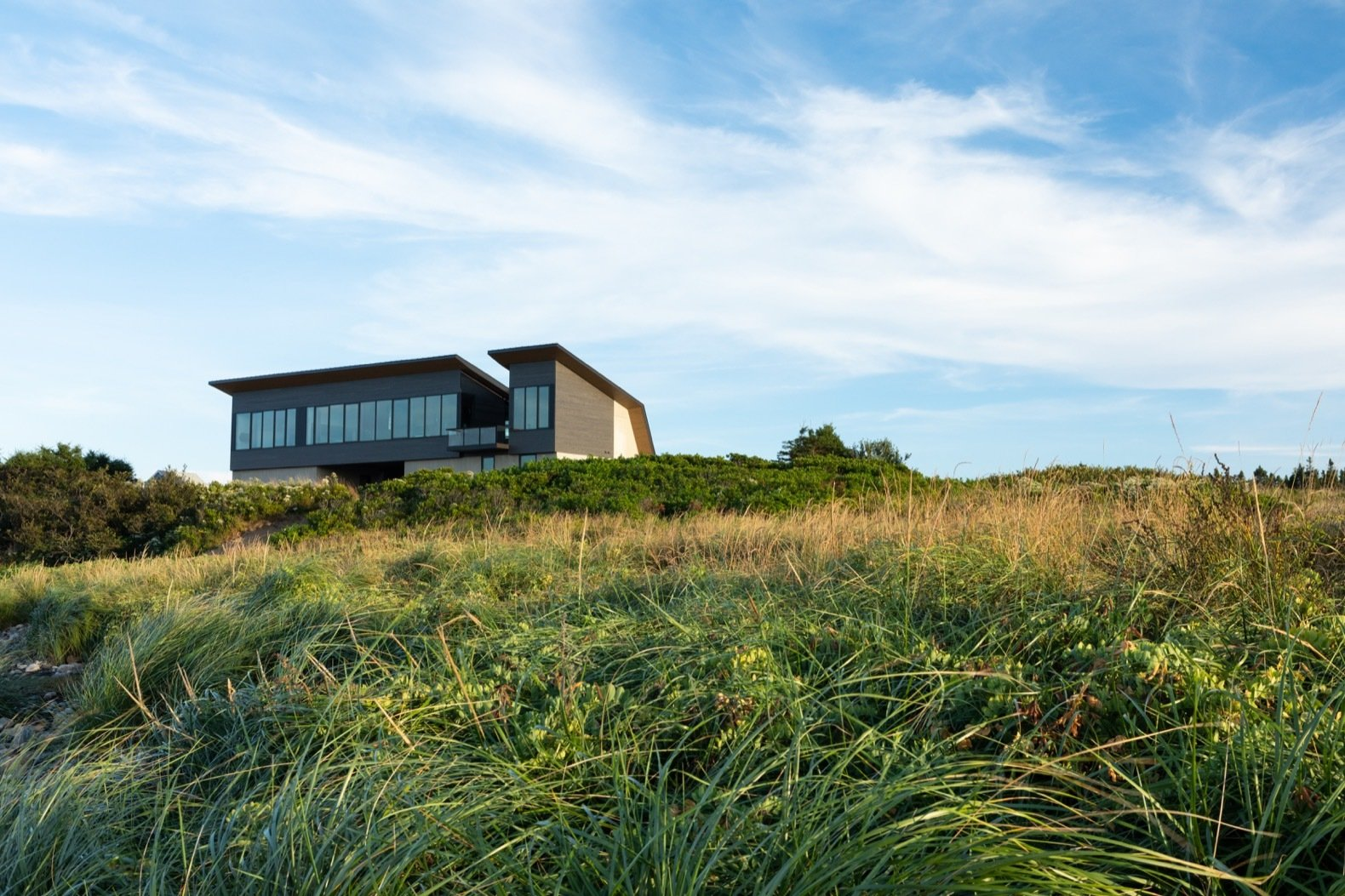 Exterior, Metal, Metal, Concrete, House, Wood, and Saltbox Located on the southern shore of Nova Scotia in Kingsburg, Treow Brycg is set in wild landscape of rocks, the sea, and tall grasses.  Exterior Metal Saltbox Concrete Photos from A Folded Steel Roof Shields a Fortress-Like Abode in Nova Scotia