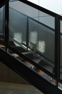 The staircase features walnut treads and black steel railings.