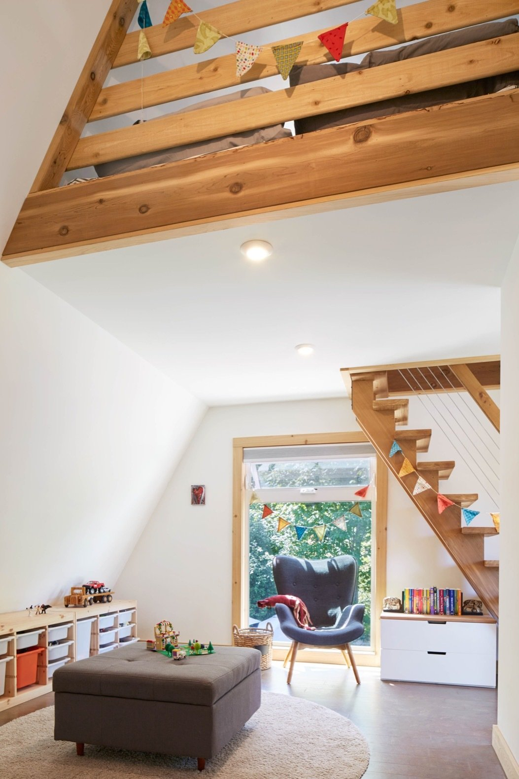 Kids Room, Storage, Chair, Pre-Teen Age, and Playroom Room Type Decorated with colorful flags handmade by Christine, the kids' light-filled play-space can easily be converted into a second bedroom.    Photo 9 of 13 in Get Cozy by the Sea in This A-Frame Cabin Asking $649K