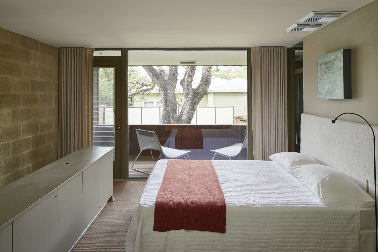 Bedroom, Bed, Floor Lighting, and Chair Located above the kitchen and dining area, the loft bedroom includes a walk-in closet, bathroom, and access to the second-floor balcony, which is framed by full-height glazing.    Photo 5 of 14 in Own an Iconic Midcentury in Austin For Just Under $500K