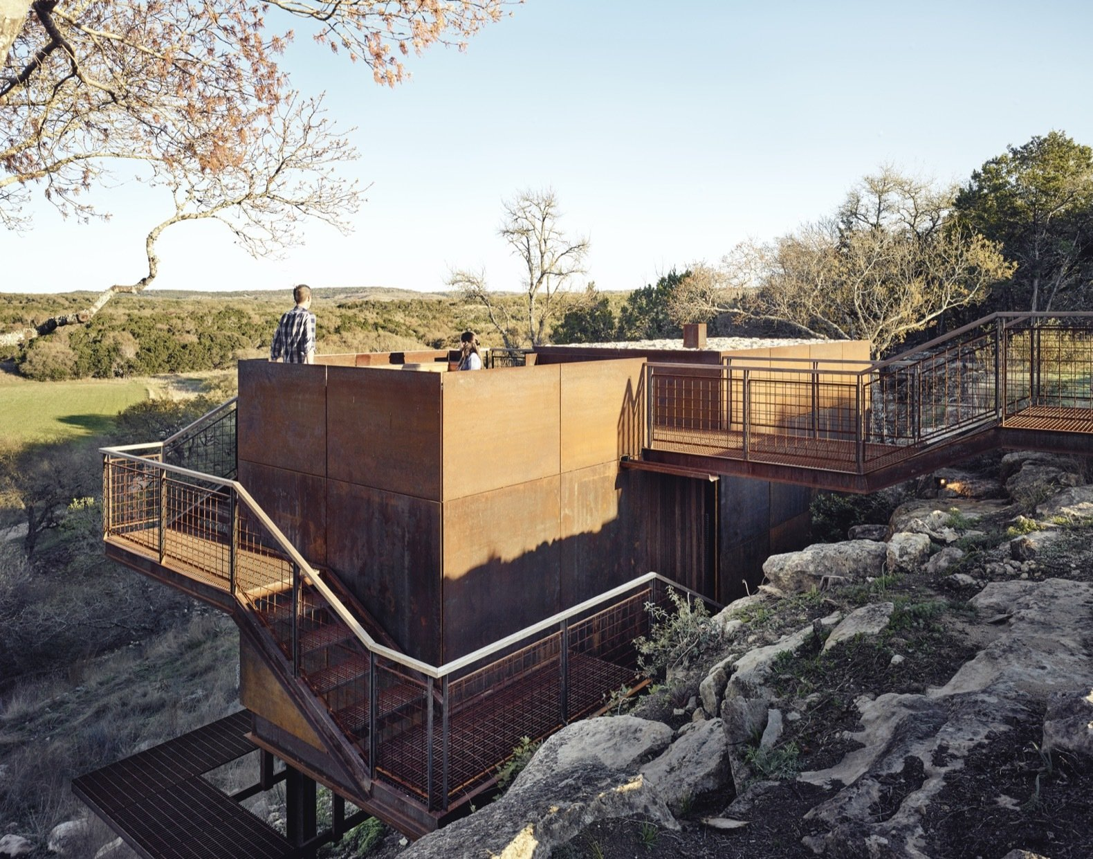 Outdoor, Walkways, Shrubs, Stone, Small, Boulders, Metal, Metal, Rooftop, and Trees The weathering steel exterior pays homage to the owner's youth, which was spent welding oil tanks.    Outdoor Metal Shrubs Metal Photos from An Award-Winning Writing Studio Hides Quietly in Texas