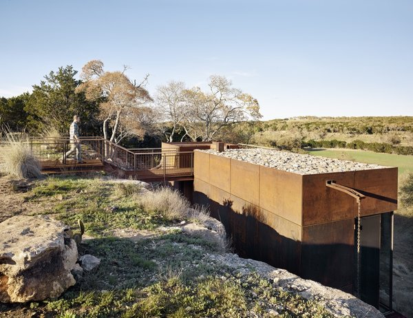 A grated metal footbridge with hog-wire, guard-rail panels connects the top of the mesa from the west side to the observation deck. Stairs lead to the glazed studio and hunting blind below.
