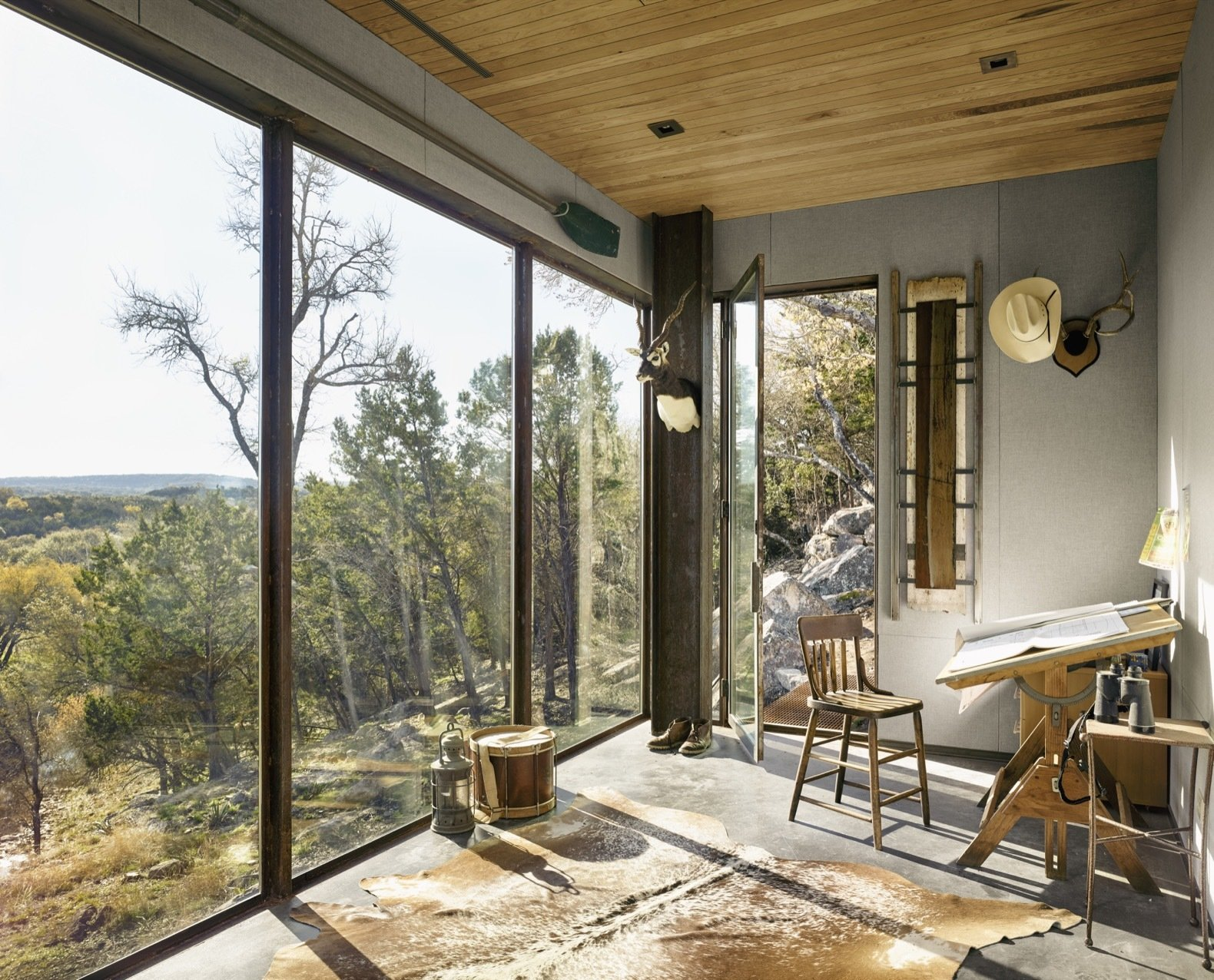 """Office, Study Room Type, Chair, Concrete Floor, and Desk The interiors were designed with a """"minimal and rustic Texas feel,""""  say the architects. The ceiling is tongue-and-groove pecan wood.  Photo 5 of 12 in An Award-Winning Writing Studio Hides Quietly in Texas"""