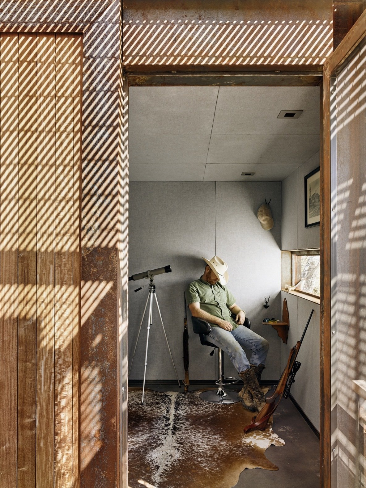 Office, Chair, Concrete Floor, Rug Floor, and Study Room Type The hunting blind is a small and square room, furnished with a cowhide rug, two guest chairs, and a hunting bar.    Photo 7 of 12 in An Award-Winning Writing Studio Hides Quietly in Texas
