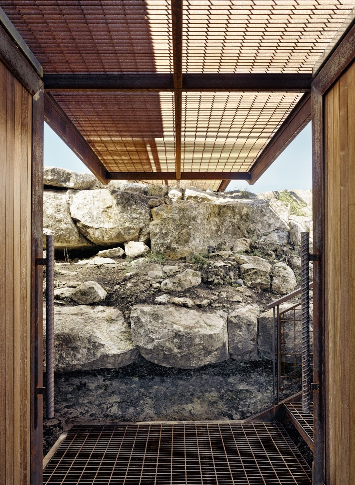 Outdoor, Small Patio, Porch, Deck, Walkways, Boulders, and Metal Patio, Porch, Deck A glimpse of the breezeway beneath the grated metal footbridge. The doors and accents were constructed from ipe wood.  Photo 6 of 12 in An Award-Winning Writing Studio Hides Quietly in Texas