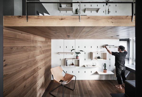 Hidden storage and flexible living are prioritized in this modern apartment of just 500 square feet in Taipei. Clever space-saving strategies and smart style choices by Taiwanese firm KC Design Studio created a chic, multifunctional home. The pegboard wall makes it easy for client Mr. Xiao to reorganize whenever needed. Anchoring the office is a chic Paulistano lounge chair by Objekto in the corner.
