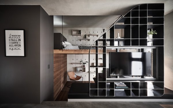 The custom shelving and staircase divides the bedroom and workspace from the living areas.