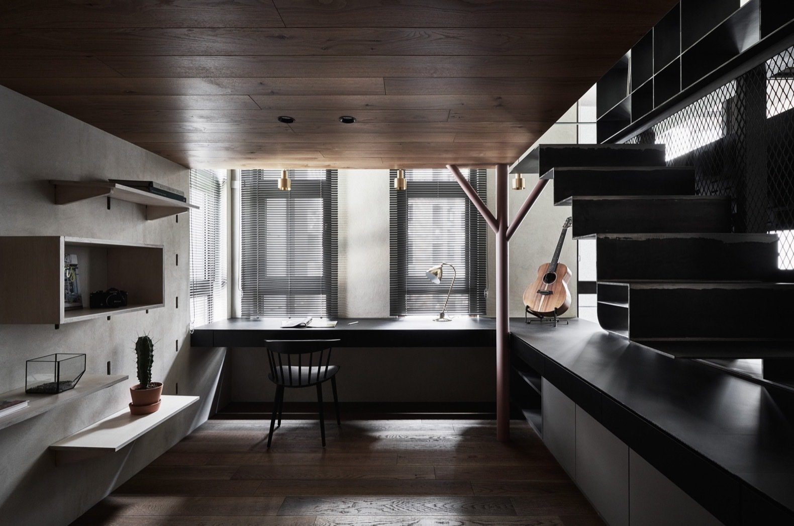 Office, Desk, Medium Hardwood Floor, Chair, Study Room Type, and Shelves The sunken workspace enjoys access to ample natural light and is flanked by three windows.   Photo 3 of 12 in A Tiny Apartment Transforms Into a Stylish, Space-Saving Bachelor Pad For $84K