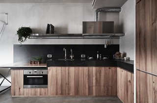 The minimalist kitchen features Slate Lite counters, timber cabinetry, and even a built-in oven, which is a luxury in Taiwan.