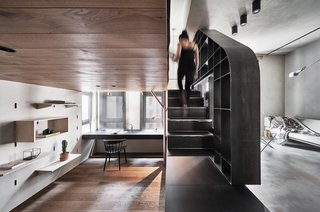 The black staircase and storage wall act as a threshold between the bedroom/office and the living spaces. Concrete-like faux finishes were used for the walls and floors of the living spaces.