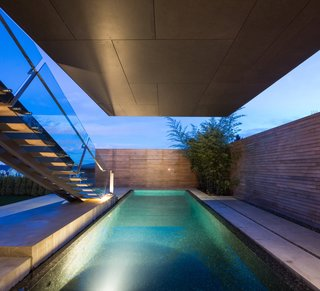 The swimming pool's dark tile finish mirrors the cantilevered container above it.