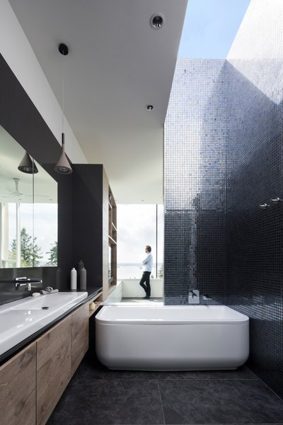 A skylight pours an abundance of natural light into the master bath, which is outfitted with a Laufen bathtub.