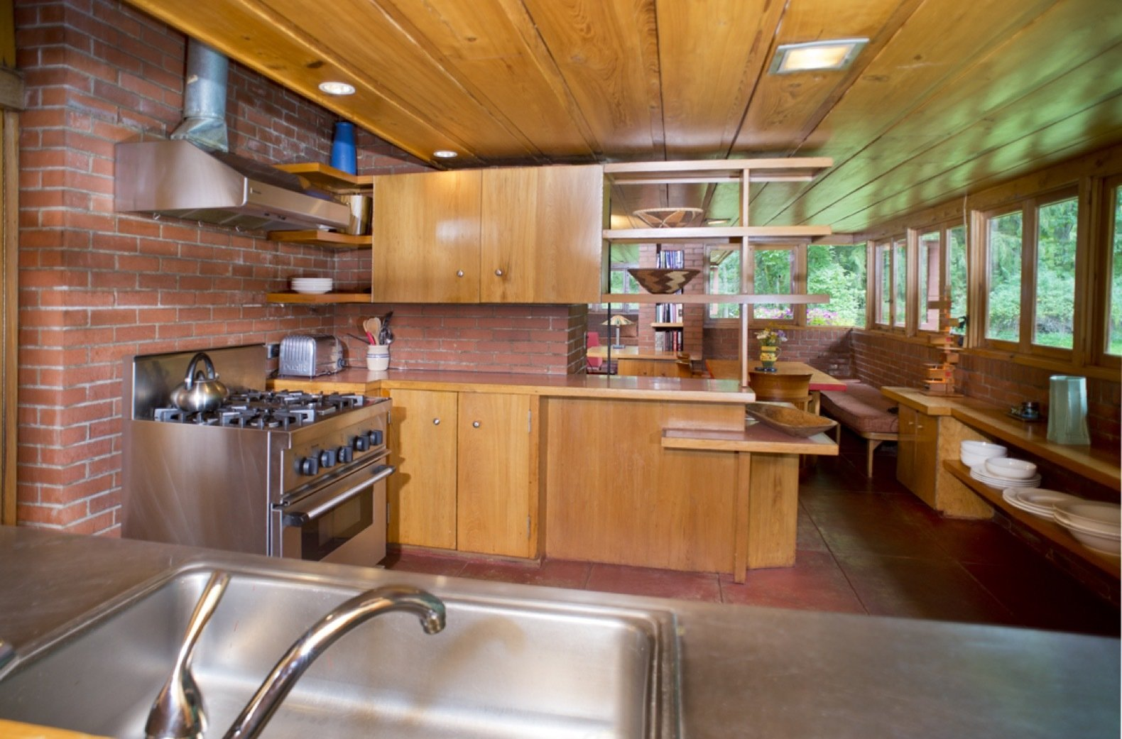 Kitchen, Refrigerator, Cooktops, Wall Oven, Wood, Range Hood, Brick, Range, Concrete, Drop In, Open, and Recessed Here is the kitchen in the south end of the home next to the dining area.   Best Kitchen Recessed Wall Oven Wood Concrete Refrigerator Photos from New Jersey's Oldest and Largest Frank Lloyd Wright House Cuts Price to $1.45M