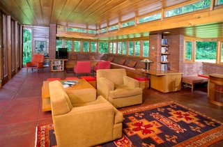 The living room and dining area features original built-in seating, tables, and chairs designed by Frank Lloyd Wright.