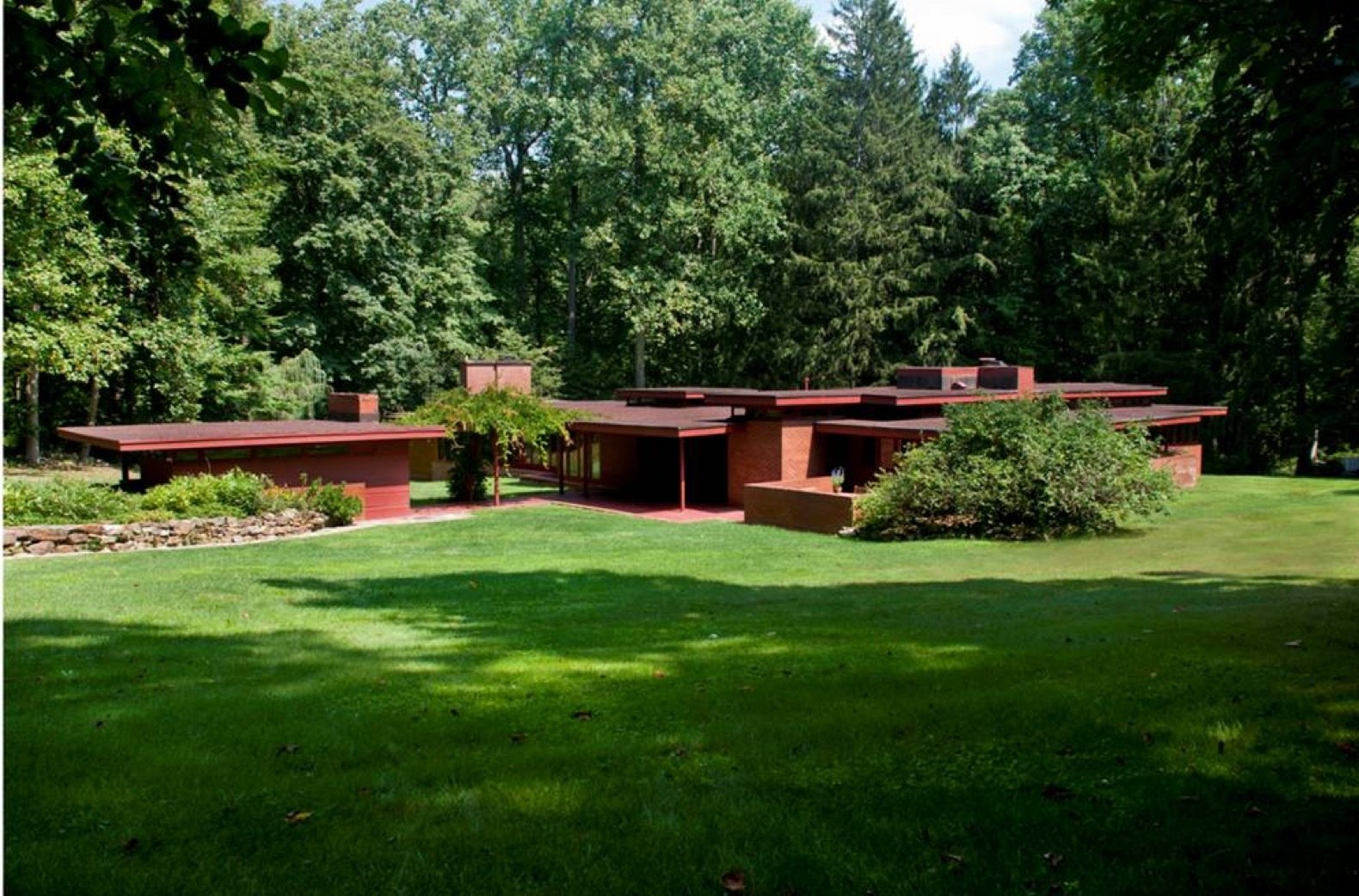Exterior, Wood Siding Material, Flat RoofLine, Glass Siding Material, Brick Siding Material, and House Building Type The view of the house seen from the driveway. To the left is the workshop and wood shed connected to the carport by a trellis.  Photo 2 of 12 in New Jersey's Oldest and Largest Frank Lloyd Wright House Cuts Price to $1.45M