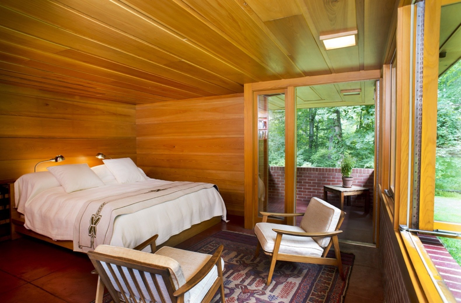 Bedroom, Table, Bed, Concrete, Ceiling, and Chair The master bedroom suite realized by Tarantino Architect opens up to an enclosed brick patio.  Best Bedroom Concrete Chair Photos from New Jersey's Oldest and Largest Frank Lloyd Wright House Cuts Price to $1.45M
