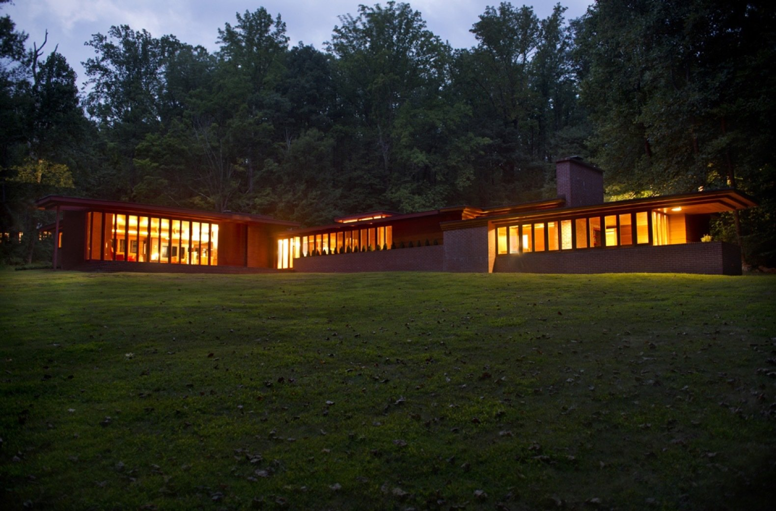 Exterior, House, Wood, Flat, Brick, and Glass A nighttime view of the home seen from the northeast. To the right is the bedroom wing extending north. To the left is the living room wing stretching to the east.  Best Exterior Glass Brick Wood Photos from New Jersey's Oldest and Largest Frank Lloyd Wright House Cuts Price to $1.45M