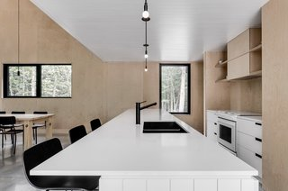 This kitchen is an exercise in light and dark, which echoes the home's dark exterior and light interior. The white quartz countertops gleam against the black sink and fixtures, and the cabinets and backsplashes were constructed from Baltic birch.