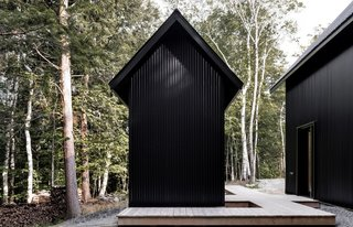 The home also includes a small outbuilding that echoes the main building's monochromatic, gabled form.