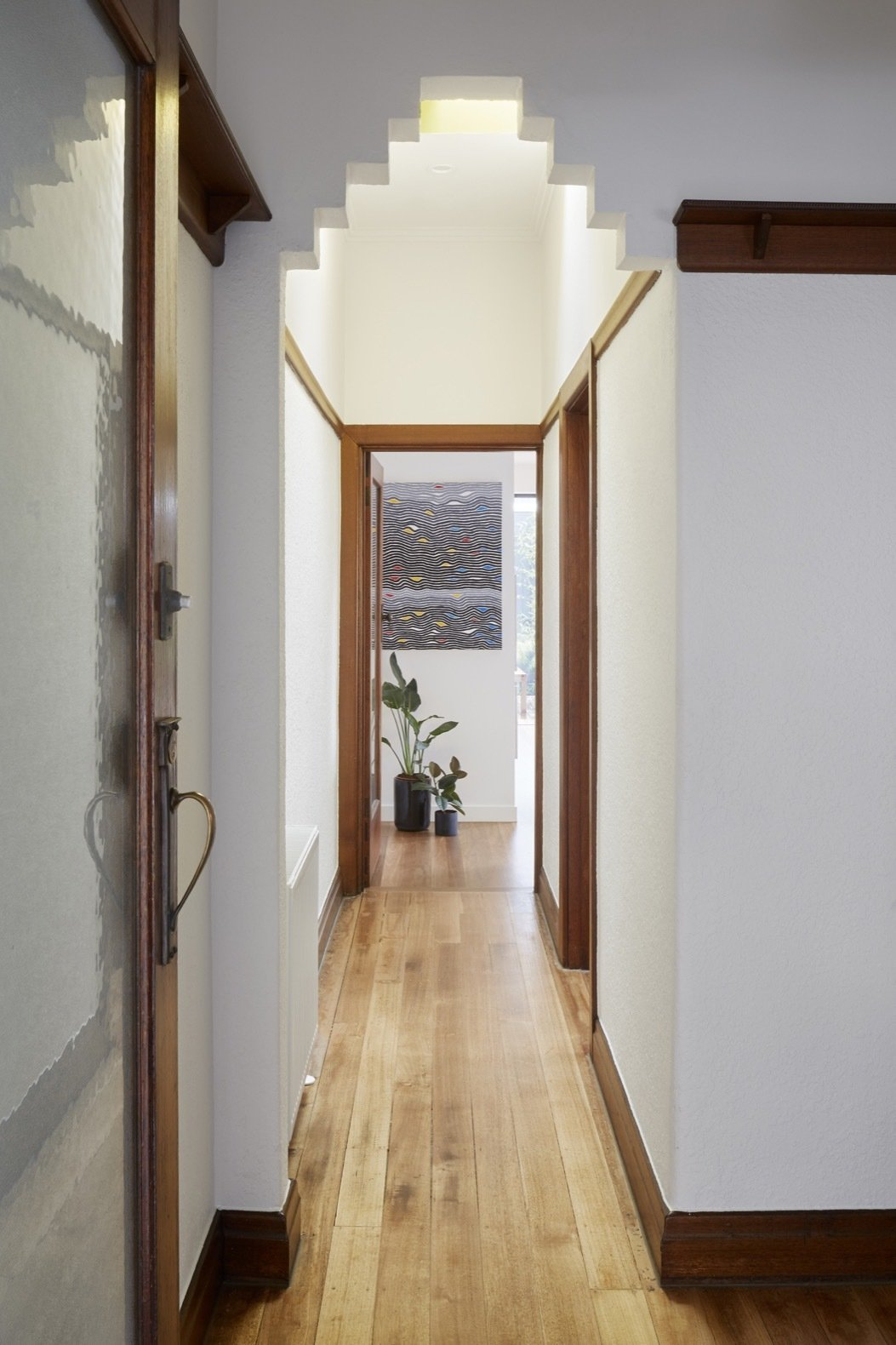 Hallway and Medium Hardwood Floor The original Art Deco style can be seen in the interior arch openings.  Photo 10 of 16 in An Art Deco Dwelling Receives a Sleek, Contemporary Extension