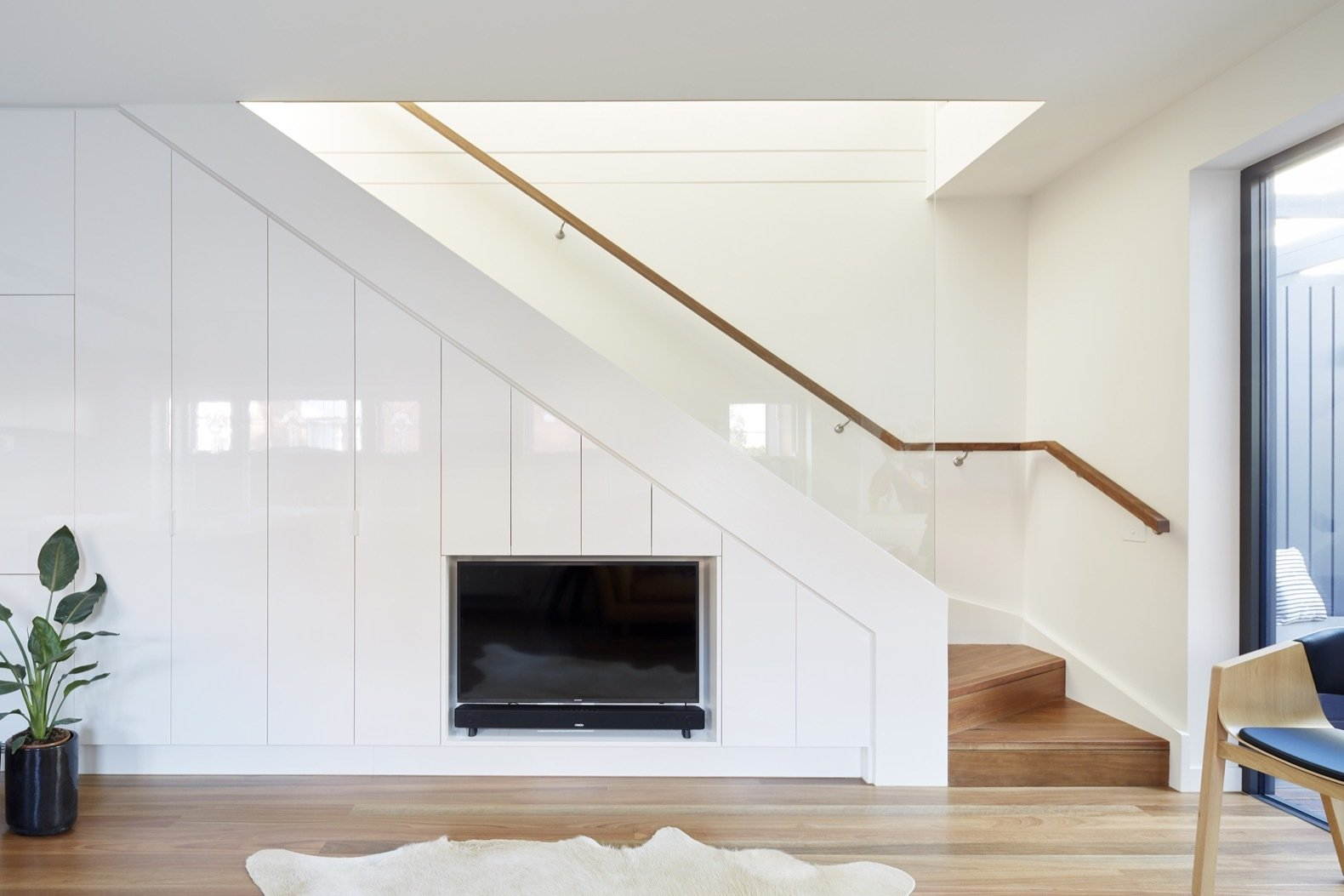 The stairs to the upper floor are bathed in natural light, thanks to a large skylight placed on the north side of the extension's roof.  Photo 11 of 16 in An Art Deco Dwelling Receives a Sleek, Contemporary Extension